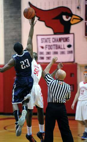 At left, Darryle Wiggins # 23 of Staples jumps center against Leonel Hyatt # 54 of Greenwich at the start of the boys high school basketball game between Greenwich High School and Staples High School at Greenwich, Tuesday, Feb. 12, 2013. Photo: Bob Luckey / Greenwich Time