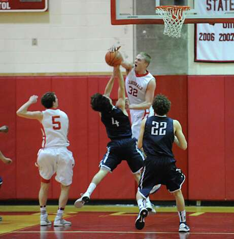 Alex Wolf # 32 of Greenwich blocks the shot of James Frsuciante # 4 of Staples during the boys high school basketball game between Greenwich High School and Staples High School at Greenwich, Tuesday, Feb. 12, 2013. At left is Jon Palmer # 4 of Greenwich, at right is Nicolaas Esposito # 22 of Staples. Photo: Bob Luckey / Greenwich Time