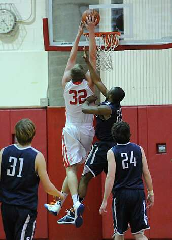 Alex Wolf # 32 of Greenwich is fouled by Darryle Wiggins # 23 of Staples while attempting a dunk during the boys high school basketball game between Greenwich High School and Staples High School at Greenwich, Tuesday, Feb. 12, 2013. At left is Peter Rankowitz, # 31, and his Staples teammate Ross Whelan # 24. Photo: Bob Luckey / Greenwich Time