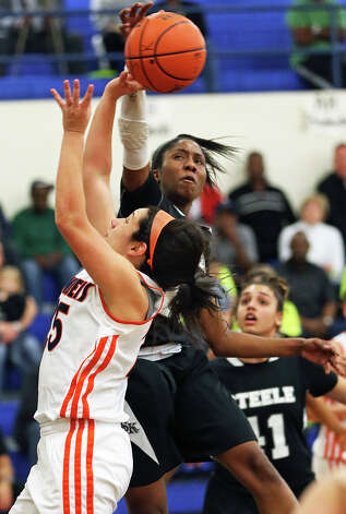 Knight forward Erika Chapman rejects the shot of Julia Cisneros in the first half as  as  Steele plays Brandeis at Alamo Heights gym on February 12, 2013. Photo: Tom Reel, San Antonio Express-News