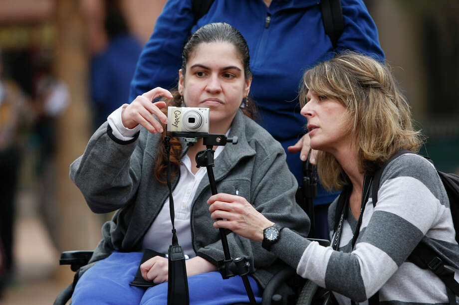 Workshop organizer, Courtney Bent, right, teaches Gabrielle Howard, 29, how to use a camera that is attached to her wheelchair as a group of special needs adults participates in a photo shoot at the Houston Zoo. Photo: Johnny Hanson, Staff / © 2013  Houston Chronicle