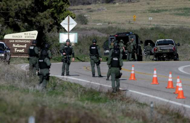 Law Enforcement personnel gear up along Hwy 38 during the hunt for accused killer and fired Los Angeles police officer, Christopher Dorner in Yacaipa, Caif.,Tuesday, Feb. 12, 2013. Dorner, a man police believe to be the fugitive ex-Los Angeles officer wanted in three killings, was barricaded inside a burning cabin Tuesday after a shootout in a California mountain town that left one deputy dead and another wounded. (AP Photo/Chris Carlson) Photo: Chris Carlson