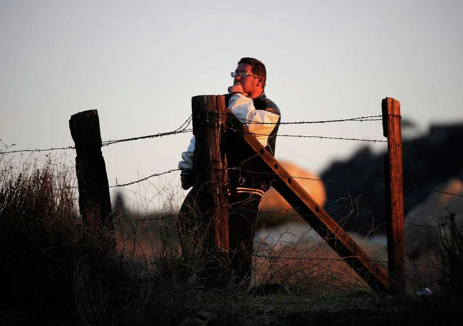 YUCAIPA, CA - FEBRUARY 12:  A resident of Redlands looks at a police blockade during a manhunt for the former Los Angeles Police Department officer Christopher Dorner, who is suspected of triple murder, on February 12, 2013 in Yucaipa, California. Dorner barricaded himself in a cabin near Big Bear, California and is in a standoff with authorities after shooting two police officers, killing one and wounding the other. Dorner, a former Los Angeles Police Department officer and Navy Reserve veteran, is wanted in connection with the deaths of an Irvine couple and a Riverside police officer. Photo: Kevork Djansezian, Getty Images / 2013 Getty Images