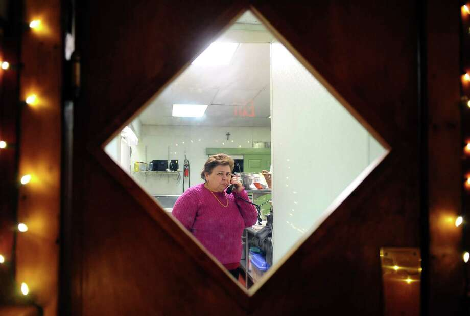 Restaurant owner Maria Moura takes a phone call at O'Manel Restaurant Tuesday, Feb. 12, 2013.  Moura has run her Portuguese restaurant at the corner of Main and Grand streets in Bridgeport, Conn. since 1977 but is appalled at the city's poor response to the recent storm. Photo: Autumn Driscoll