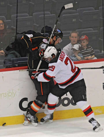 From left, Peter Holland of Syracuse battles for the puck with Matt Anderson of the Albany Devils during a hockey game at the Times Union Center Wednesday, Dec. 14, 2011 in Albany, N.Y.  Devils lost in overtime. (Lori Van Buren / Times Union) Photo: Lori Van Buren / 00015748A