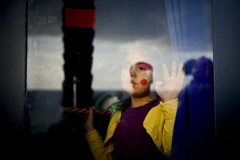 TOPSHOTS A girl with make-up on her face watches the clown parade through a window in Sesimbra, on February 11, 2013.     AFP PHOTO/ PATRICIA DE MELO MOREIRAPATRICIA DE MELO MOREIRA/AFP/Getty Images Photo: Patricia De Melo Moreira, AFP/Getty Images