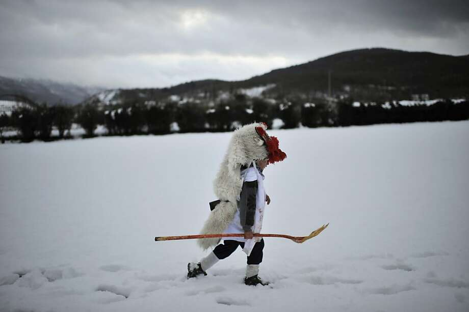 A boy dressed up as Momotxorro, a local mythical animal, walks in the snow during carnival celebrations in Alsasua, northern Spain, Tuesday, Feb. 12, 2013. (AP Photo/Alvaro Barrientos) Photo: Alvaro Barrientos, Associated Press