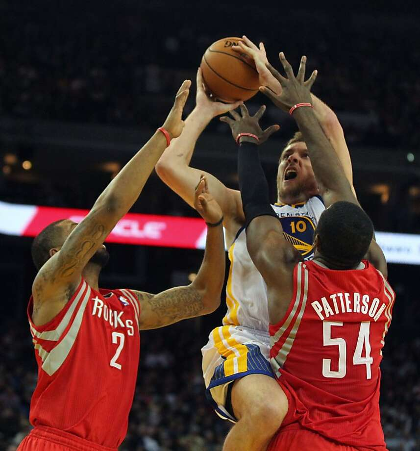 Golden State Warriors forward David Lee (10) shoots between two Houston Rockets defenders in the first half of their NBA basketball game Tuesday, February 13, 2013. in Oakland Calif. Photo: Lance Iversen, The Chronicle