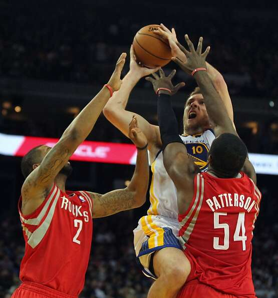 Golden State Warriors forward David Lee (10) shoots between two Houston Rockets defenders in the fir