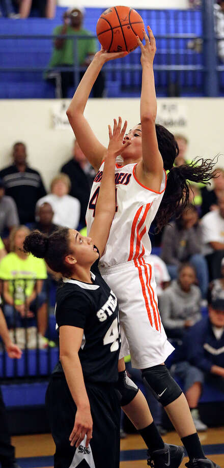 Brandeis center Morgan Williams puts up a shot in the lane with the hand of Knight guard Bri Millett in her face as  Steele plays Brandeis at Alamo Heights gym on February 12, 2013. Photo: Tom Reel, San Antonio Express-News