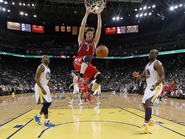 Houston Rockets' Omer Asik (3) dunks between Golden State Warriors' Jarrett Jack (2) and Carl Landry (7) during the first half of an NBA basketball game in Oakland, Calif., Tuesday, Feb. 12, 2013. (AP Photo/Marcio Jose Sanchez) Photo: Marcio Jose Sanchez, Associated Press