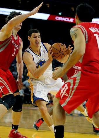 Golden State Warriors guard Klay Thompson (11) passes off between two Houston Rockets defenders in the first half of their NBA basketball game Tuesday, February 13, 2013. in Oakland Calif. Photo: Lance Iversen, The Chronicle