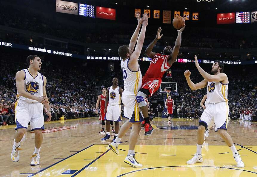 Houston Rockets' James Harden (13) shoots between Golden State Warriors' Klay Thompson (11), David L