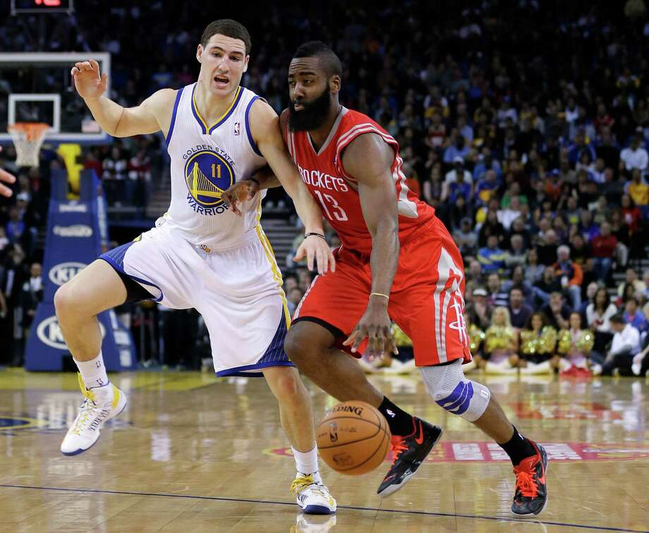James Harden, driving on Klay Thompson, shook off knee pain to score 27 points. Photo: Marcio Jose Sanchez, STF / AP