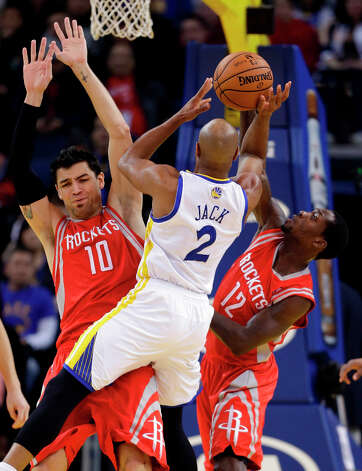 Jarrett Jack of the Warriors tries to shoot in front of Carlos Delfino of the Rockets. Photo: Marcio Jose Sanchez