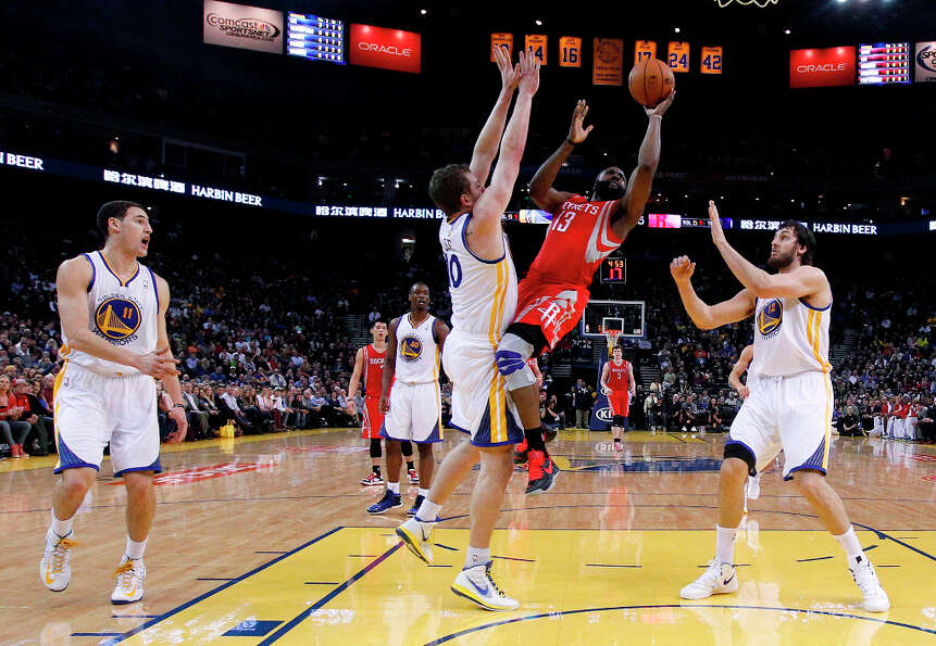 Rockets guard James Harden attempts a shot in the midst of three Warriors defenders.