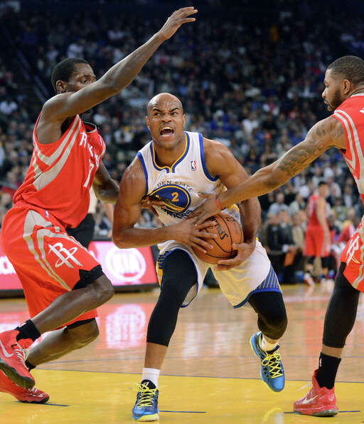 Warriors guard Jarrett Jack keeps the ball away from Patrick Beverley and Marcus Morris of the Rocke