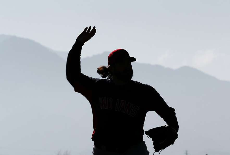 Cleveland Indians pitcher Chris Perez simulates throwing during spring training baseball in Goodyear