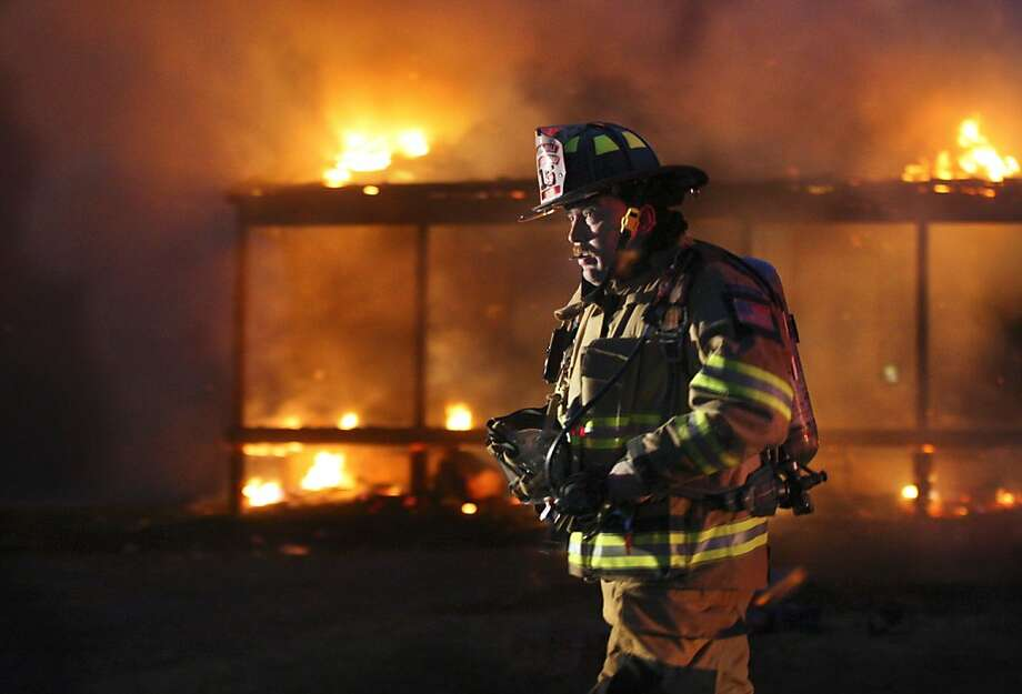 A Frederick County firefighter walks past the front of a burning home Tuesday, Feb. 12, 2013 in Mountain Falls park west of Winchester, Va. (AP Photo/The Winchester Star, Scott Mason) Photo: Scott Mason, Associated Press