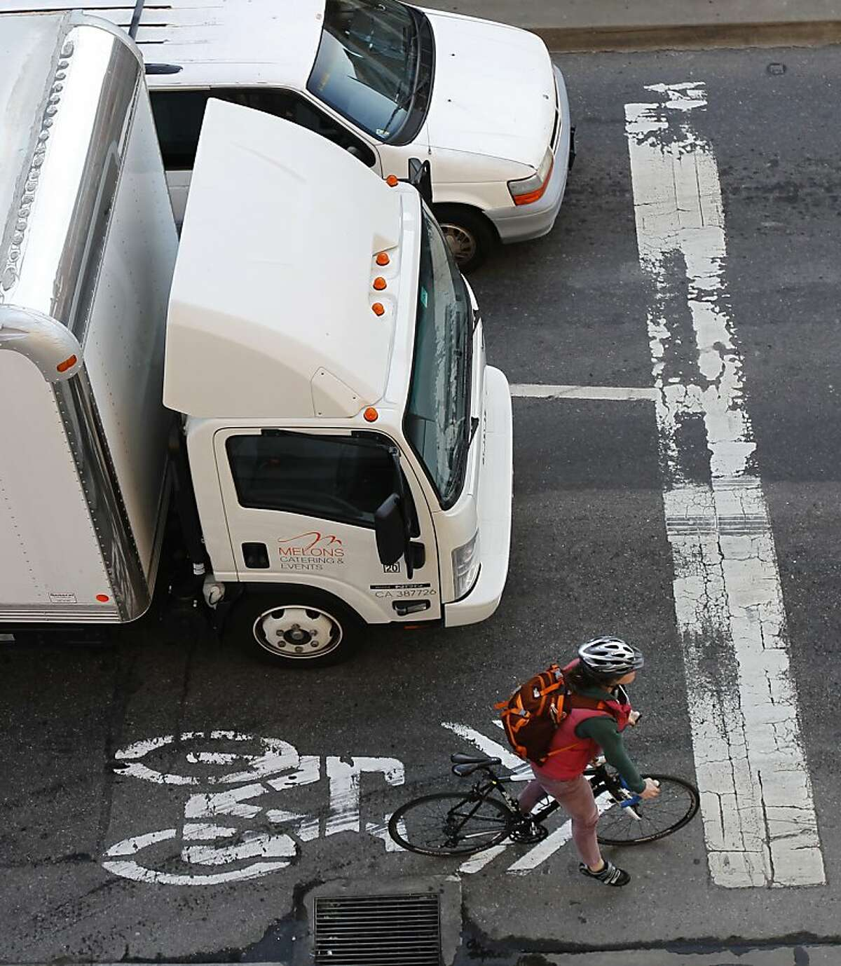 A cyclist prepares to merge into traffic near the end of the bike lane on King Street between 2nd and 3rd streets in San Francisco, Calif. on Tuesday, Feb. 12, 2013. A woman riding her bicycle was struck and killed after she collided with a cement truck last weekend.