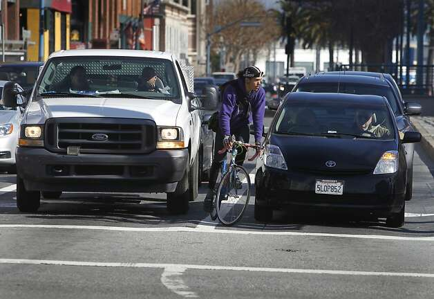 A bicyclist waits to turn south onto Third Street after the bike lane ends on King Street in San Francisco, Calif. on Tuesday, Feb. 12, 2013. A woman riding her bicycle was struck and killed after she collided with a cement truck last weekend. Photo: Paul Chinn, The Chronicle