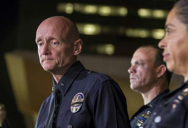 Los Angeles Police Commander Andrew Smith, left, expresses condolences for the death of a San Bernardino County deputy, as he briefs the media about the shootout scene in Big Bear that allegedly involves triple-murder suspect Christopher Jordan Dorner, during a late news conference in front of the Police Administration Building in Los Angeles, Tuesday, Feb. 12, 2013. Lt. Bill Whalen, of the Irvine Police Department, middle and LAPD officer Norma Eisenman, right, stand with Smith. Photo: Damian Dovarganes