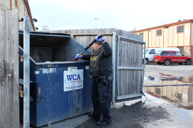 A Houston police officer searches a Dumpster at an apartment complex on Sunnyside near Werner Wednesday, Feb. 13, 2013. Officers asked the trash company to hold off on pickup until their search for a newborn baby is completed. Photo: Nick De La Torre / Houston Chronicle