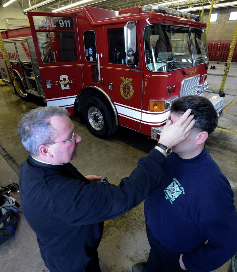 Albany Fire Department Chaplain Rev. John Tallman places ashes on the forehead of Engine 2 firefighter Matt Robbins at the Arbor Hill fire station as part of the Ash Wednesday observance Feb. 13, 2013, in Albany, N.Y.   Firefighters who observe the Catholic religious tradition received ashes in their fire stations throughout the City of Albany from Father Tallman.  (Skip Dickstein/Times Union) Photo: SKIP DICKSTEIN