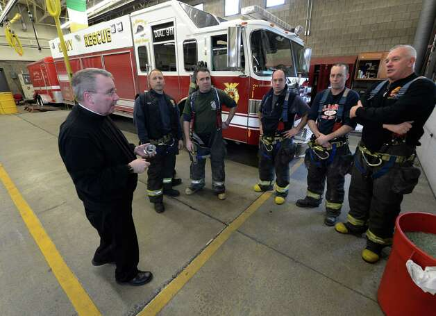 Members of the Rescue Squad line up for Albany Fire Department Chaplain Rev. John Tallman to receive ashes as part of the Ash Wednesday observance Feb. 13, 2013, in Albany, N.Y.   Firefighters who observe the Catholic religious tradition received ashes in their fire stations throughout the City of Albany from Father Tallman.  (Skip Dickstein/Times Union) Photo: SKIP DICKSTEIN