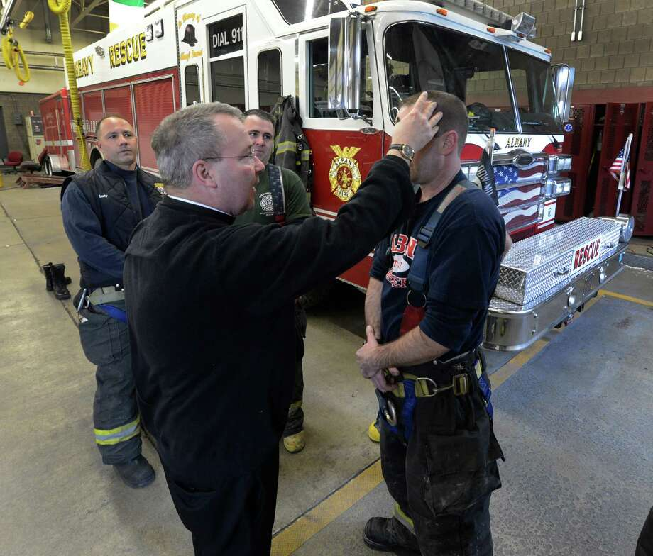 Kevin Hicks, right, and other members of the Rescue Squad line up for Albany Fire Department Chaplain Rev. John Tallman to receive ashes as part of the Ash Wednesday observance Feb. 13, 2013, in Albany, N.Y.   Firefighters who observe the Catholic religious tradition received ashes in their fire stations throughout the City of Albany from Father Tallman.  (Skip Dickstein/Times Union) Photo: SKIP DICKSTEIN