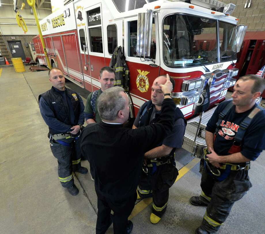Louis Forezzi, second from right, and other members of the Rescue Squad receive ashes from Albany Fire Department Chaplain Rev. John Tallman as part of the Ash Wednesday observance Feb. 13, 2013, in Albany, N.Y.   Firefighters who observe the Catholic religious tradition received ashes in their fire stations throughout the City of Albany from Father Tallman.  (Skip Dickstein/Times Union) Photo: SKIP DICKSTEIN