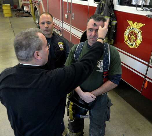 Chris VonDollen, right, and other members of the Rescue Squad received ashes from Albany Fire Department Chaplain Rev. John Tallman as part of the Ash Wednesday observance Feb. 13, 2013, in Albany, N.Y.   Firefighters that observe the Catholic religious tradition received ashes in their fire stations throughout the City of Albany from Father Tallman.  (Skip Dickstein/Times Union) Photo: SKIP DICKSTEIN