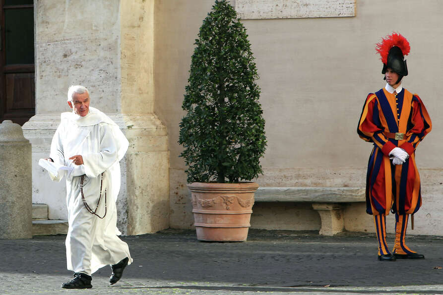 A friar  walks at the Cortile di San Damaso of the Apostolic Palace at the Apostolic Palace on Decem