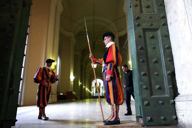 Swiss guards stand on attention at the Portone di Bronzo of the Apostolic Palace on October 29, 2012 in Vatican City, Vatican. Pope Sixtus V (1585- 1590) built the Apostolic Palace where the present pope lives and where every Sunday at noon he stands at the window, and blesses the crowd that gathers in the magnificent St. Peter's square. Photo: Franco Origlia, Getty Images / 2013 Franco Origlia