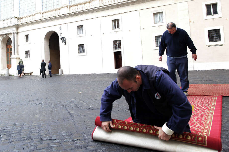 Workers set a red carpet for a visit of state at the Cortile di San Damaso of the Apostolic Palace on October 29, 2012 in Vatican City, Vatican. Pope Sixtus V (1585- 1590) built the Apostolic Palace where the present pope lives and where every Sunday at noon he stands at the window, and blesses the crowd that gathers in the magnificent St. Peter's square. Photo: Franco Origlia, Getty Images / 2013 Franco Origlia