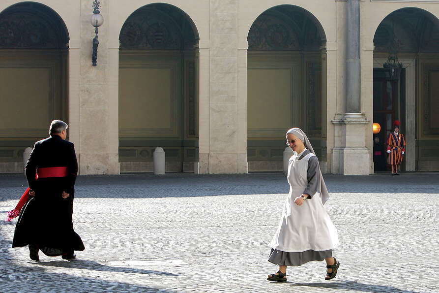A priest and a nun walk at the Cortile di San Damaso of the Apostolic Palace on October 25,  2012 in