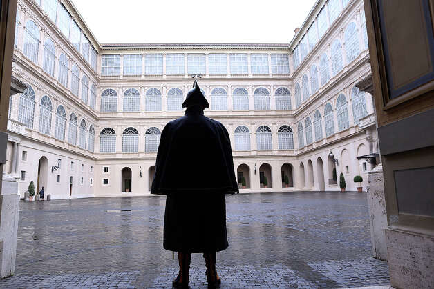 A Swiss guard stands at attention at the Cortile di San Damaso of the Apostolic Palace on October 29,  2012 in Vatican City, Vatican. Pope Sixtus V (1585- 1590) built the Apostolic Palace where the present pope lives and where every Sunday at noon he stands at the window, and blesses the crowd that gathers in the magnificent St. Peter's square. Photo: Franco Origlia, Getty Images / 2013 Franco Origlia