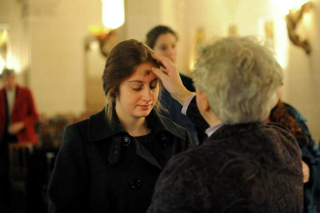 Catherine Semel-DeFeo of Albany, center, receives ashes on her forehead from Sister Eleanor Guerin on Wednesday, Feb. 13, 2013, at the Grotto of Our Lady of Lourdes in Albany, N.Y. (Cindy Schultz / Times Union) Photo: Cindy Schultz / 00021028A