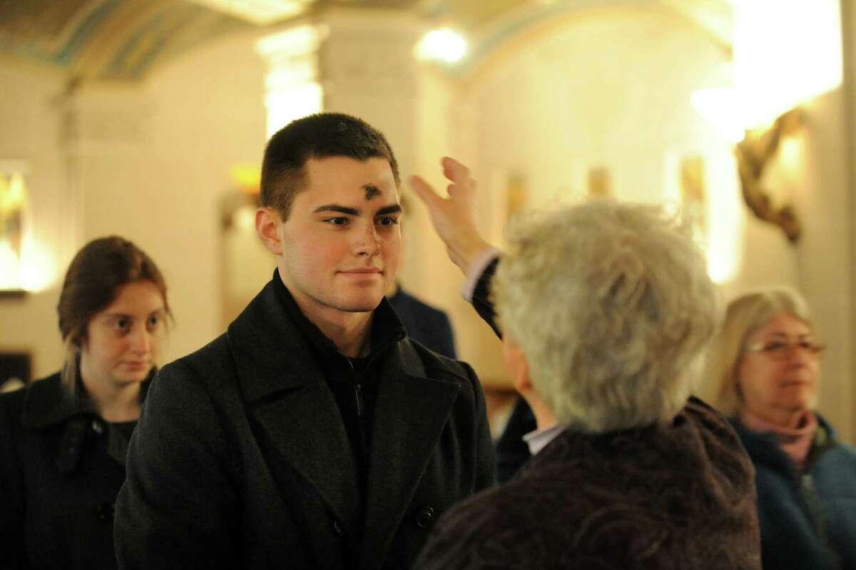 Matthew Stetler, 19, a student at the College of Saint Rose, center, receives ashes on his forehead from Sister Eleanor Guerin on Wednesday, Feb. 13, 2013, at the Grotto of Our Lady of Lourdes in Albany, N.Y. People of the Catholic faith receive ashes to mark Ash Wednesday and the start of Lent. (Cindy Schultz / Times Union)