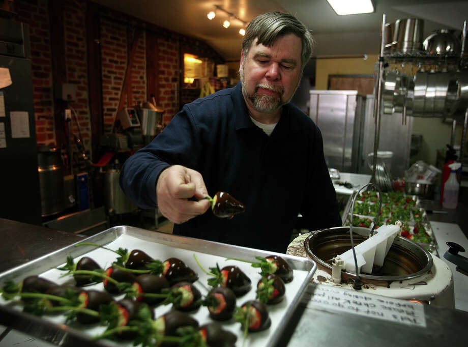 Paul Mangels, owner of H. Mangels Confectioner at 11 River Street in downtown Milford, Conn. dips lond stem strawberries in chocolate as a special for Valentine's Day on Wednesday, February 13, 2013. Photo: Brian A. Pounds / Connecticut Post