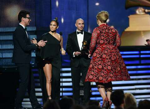 Jennifer Lopez (second from left) shoos away Vitalii Sediuk (left) as Pitbull presents Adele with the Grammy for best solo pop performance. Sediuk, a Ukrainian journalist, crashed the Grammys and now faces trespassing charges. Photo: Kevork Djansezian / Getty Images