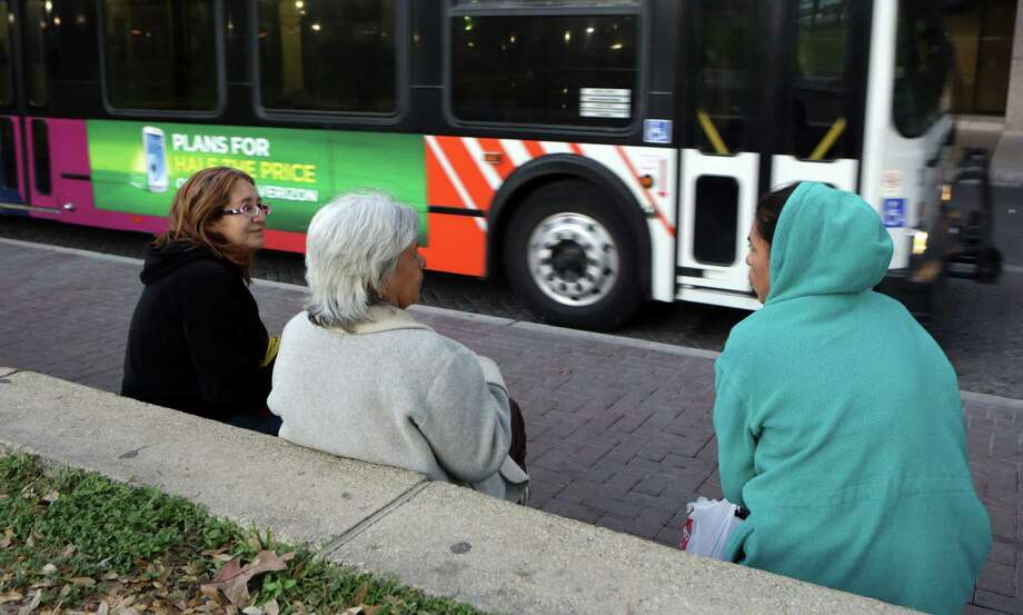 Araceli Herrera (left), a housekeeper and local activist, speaks to Sally Ramos (right) and Jaquina Ortiz as they wait for a transfer bus to take them to the North Side where they clean homes. Photo: Bob Owen / San Antonio Express-News