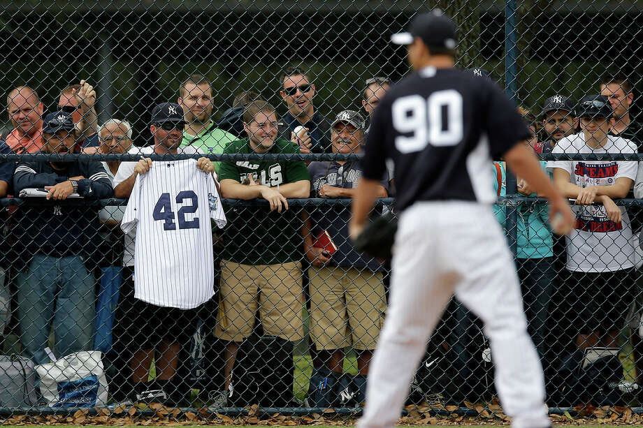 New York Yankees' fans wait for autographs as non-roster invitee Cito Culver works on pick-off moves during a workout at baseball spring training, Wednesday, Feb. 13, 2013, in Tampa, Fla. Photo: Matt Slocum, AP / AP