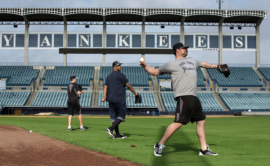 New York Yankees pitcher Joba Chamberlain, right, throws the ball during baseball spring training at George M. Steinbrenner Field Tuesday, Feb. 12, 2013, in Tampa, Fla. At center is teammate CC Sabathia. Photo: Scott Iskowitz, AP / FR170674 AP