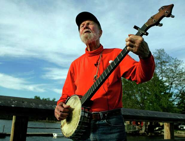 FILE - In this May 5, 2006 file photo, Pete Seeger plays his banjo by the Hudson River in his hometown of Beacon, N.Y., about 70 miles north of New York City. Beacon High School has named its theater after the 93-year-old folk singer and his wife of nearly 70 years, Toshi. (AP Photo/Frank Franklin II, File) Photo: Frank Franklin II
