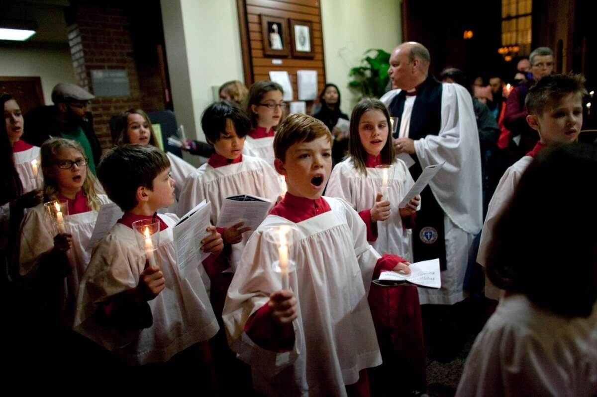 Children sing at St. Marks Cathedral during an interfaith vigil and march against gun violence on Saturday, Feb. 9, 2013 in Seattle. Hundreds of people marched with candles from St. Mark's Episcopal Cathedral, through Capitol Hill and eventually to St. James Catholic Cathedral.