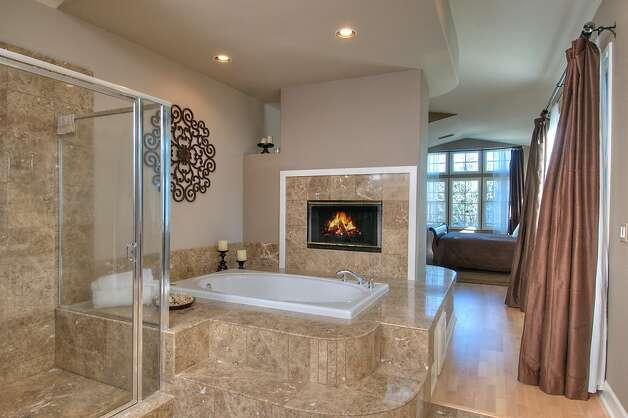 The master bathroom,has a raised tub and a fireplace. Photo: Matt McCourtney
