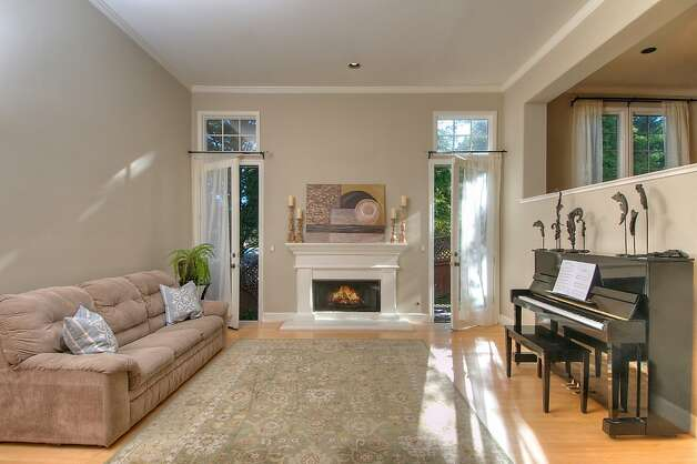 The living room features one of the home's three fireplaces and dual access to the level backyard. Photo: Matt McCourtney