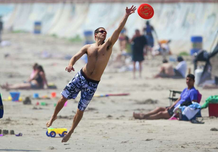 Josh Leuchtag, of Houston, reaches for a frisbee as he enjoys some sunshine with his girlfriend Lacey Truelove, of Houston, Tuesday, March 13, 2012, on the beach by Seawall Boulevard in Galveston. Photo: Nick De La Torre, Staff / 2012  Houston Chronicle