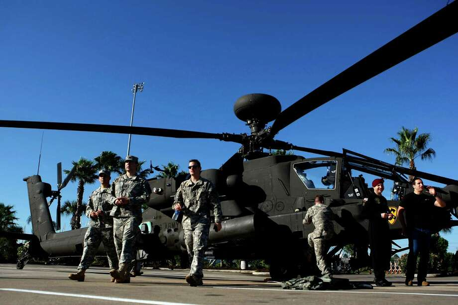 U.S. Army Air Calvary servicemen walk away from an AH-64 Apache helicopter after it landed in the parking lot at the Kemah Boardwalk last November in preparation for the Salute to Military Service weekend. The helo is similar to the one that will be used in today's Army training exercise in Texas City and La Marque. Photo: Johnny Hanson/Houston Chronicle